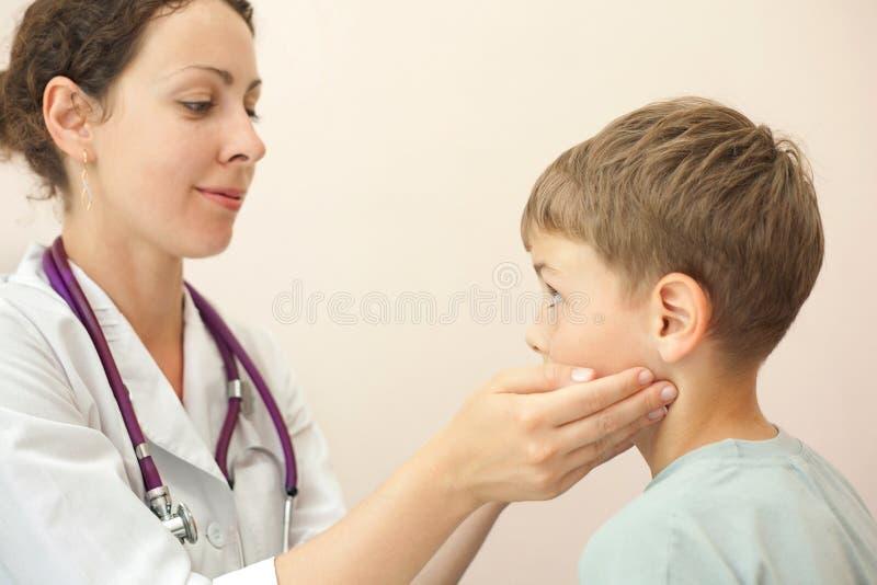 医生检查小男孩淋巴结 免版税库存图片
