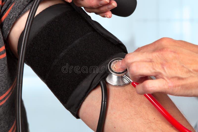 医生测量与听诊器的血压 免版税库存照片