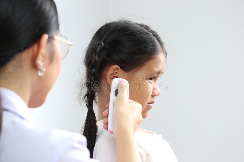 医生特写镜头审查或在耳朵的治疗儿童耐心温度使用在白色背景的电子温度计, 免版税库存照片