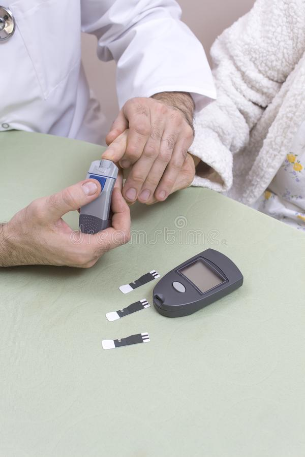 医生猛击一个非常老妇人的手指 与条纹的glucometer在桌上说谎 免版税库存照片
