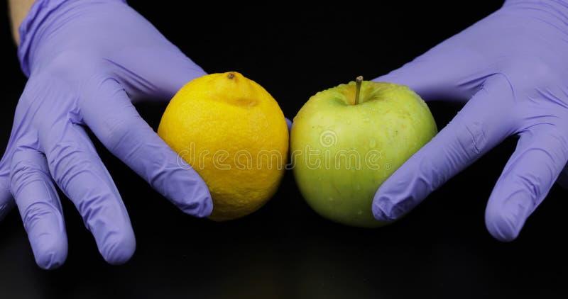医生的手用苹果和柠檬在黑背景 图库摄影