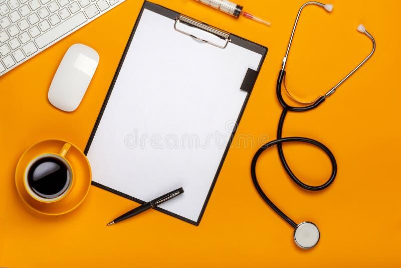 医生的桌的顶视图与笔记薄和笔听诊器、键盘、处方和药片,一杯咖啡的在黄色的 库存照片