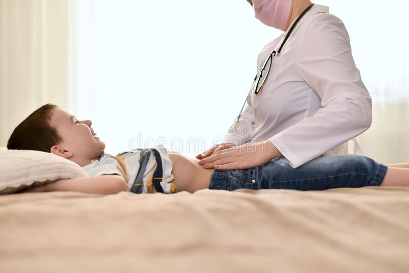 医生看一个笑的婴孩的肚子 免版税库存图片