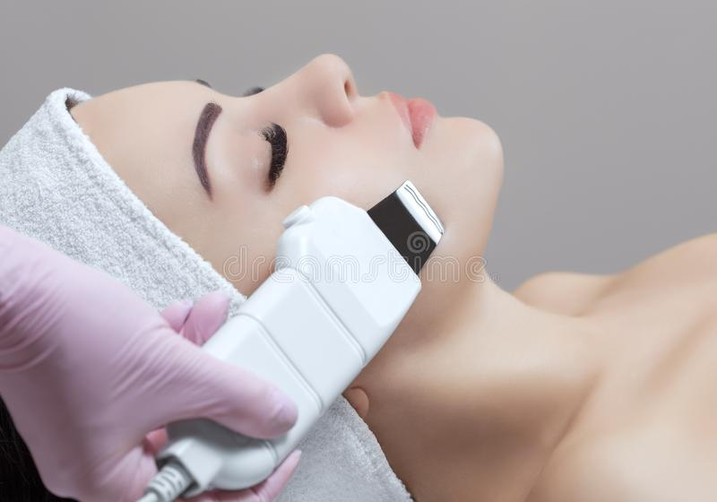 医生美容师做用具做法一个美丽,少妇的面部皮肤的超声波清洁 图库摄影