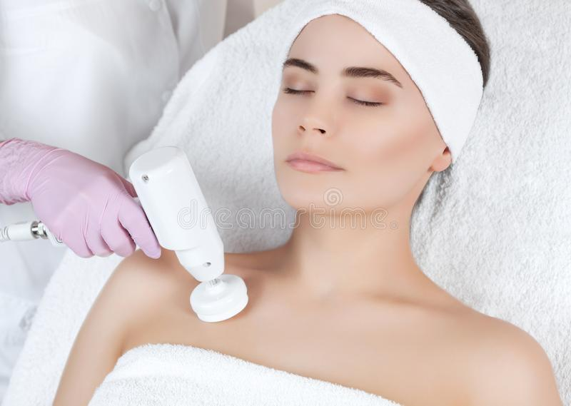 医生美容师做用具做法与一把软的转动的刷子的硬件低颈露肩的面孔清洁 库存照片