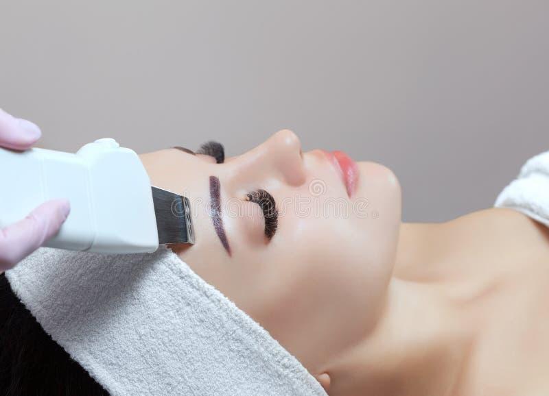 医生美容师做用具做法面部皮肤的超声波清洁 免版税库存照片