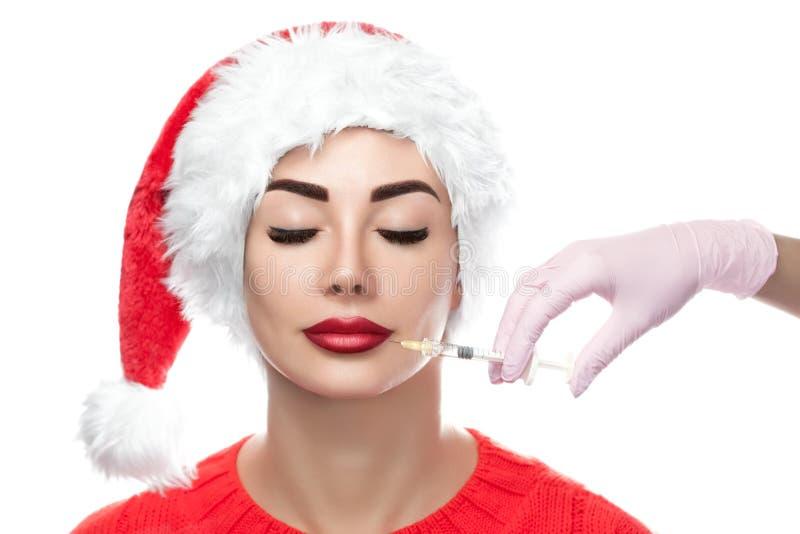 医生美容师在一名美丽的妇女的面孔皮肤做Botox射入做法圣诞老人帽子的 免版税库存照片