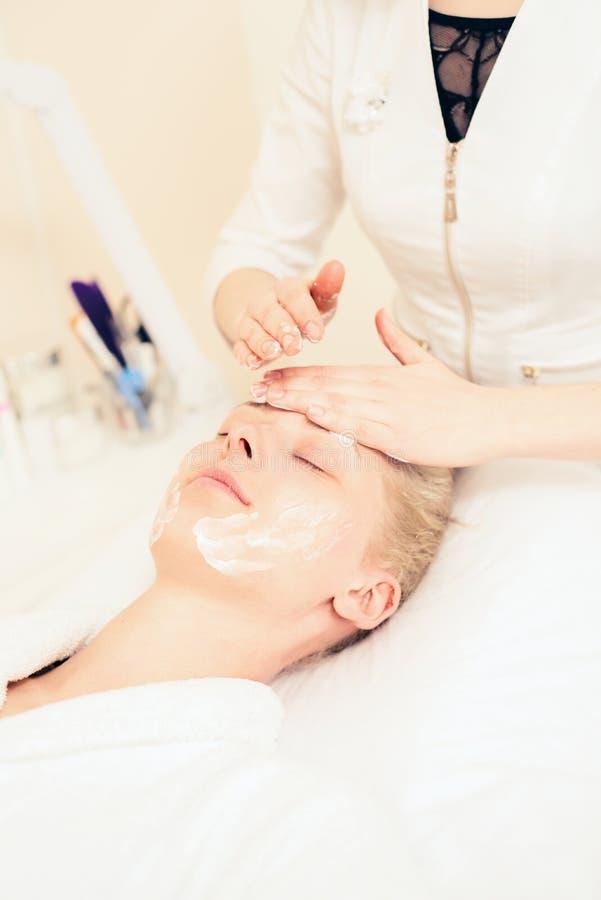 医生美容师在患者上的面孔把奶油放 温泉整容术 r 库存图片