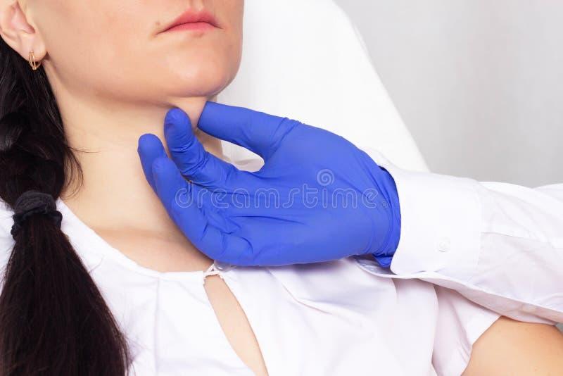 医生美容师检查皮肤在双下巴的弹性在女孩,特写镜头,整容术,韧性 免版税库存图片