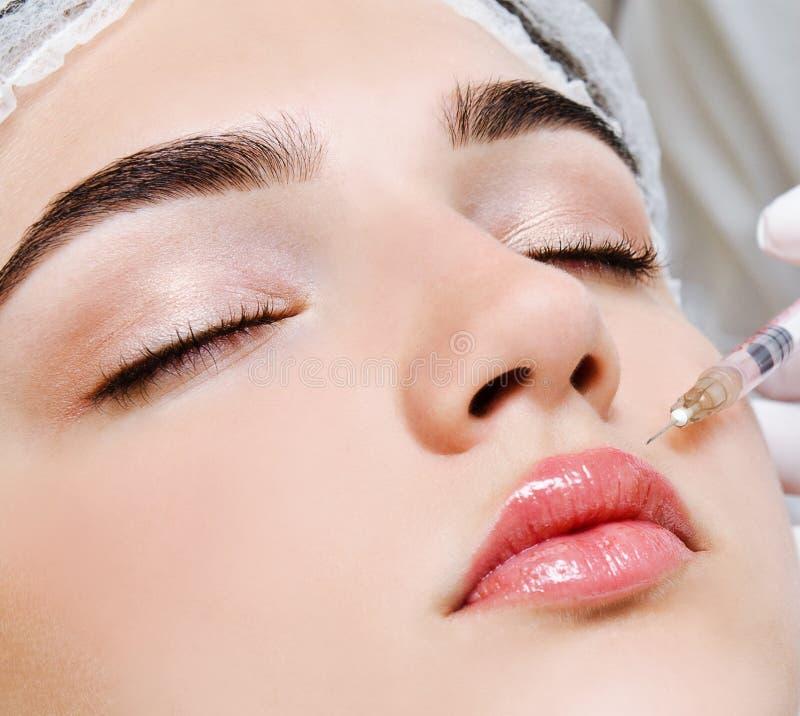 医生美容师美容师做拉紧和使的皱痕光滑使充满活力的面部botox射入方法 免版税库存照片
