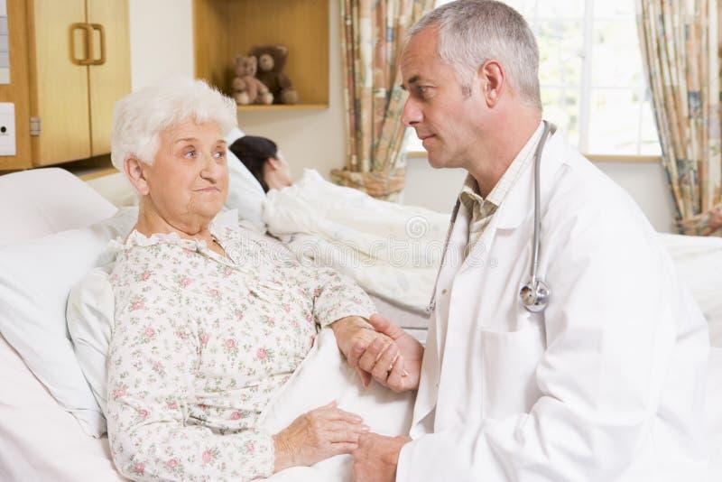 医生耐心的高级联系的妇女 免版税库存图片