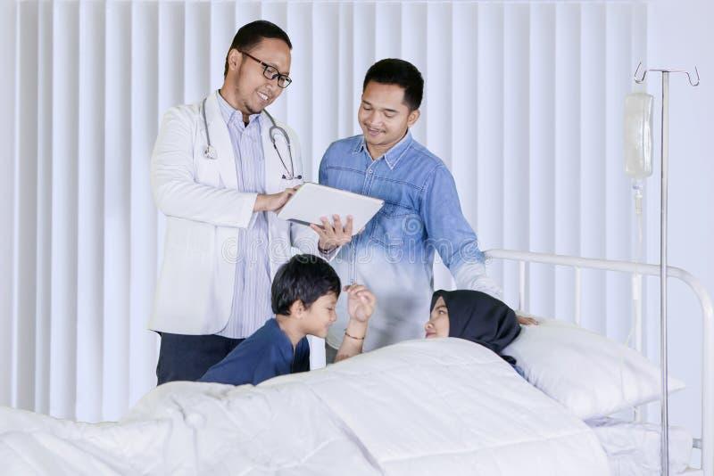 医生解释在他的耐心家庭的医疗结果 免版税库存图片