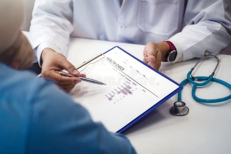 医生解释男性患者的健康检查文件诊所或医院健康的 健康和医生概念 免版税图库摄影