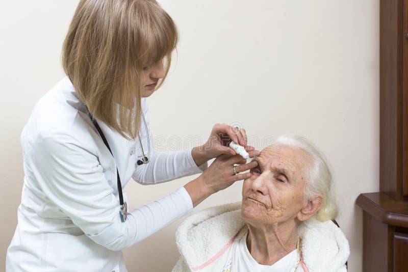 医生让下落入一个非常老妇人的眼睛坐椅子在一件白色浴巾 免版税库存照片