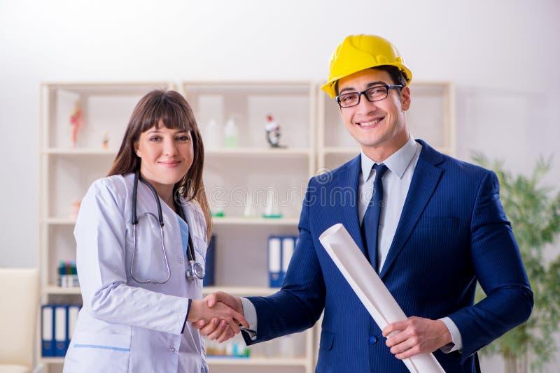 医生谈论新的医院计划与建筑师 免版税库存图片