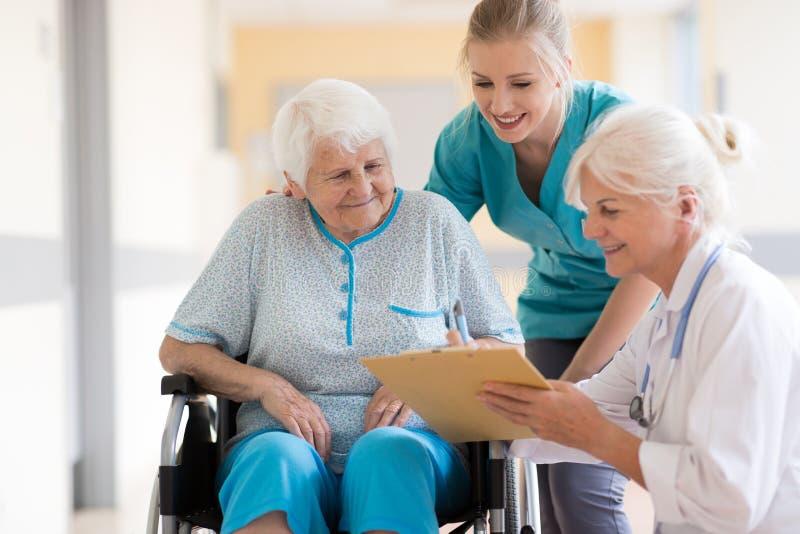 医生谈话与她的患者在医院 库存图片