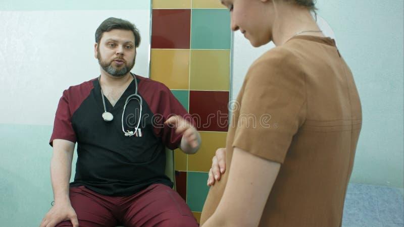 医生谈话与孕妇 库存图片