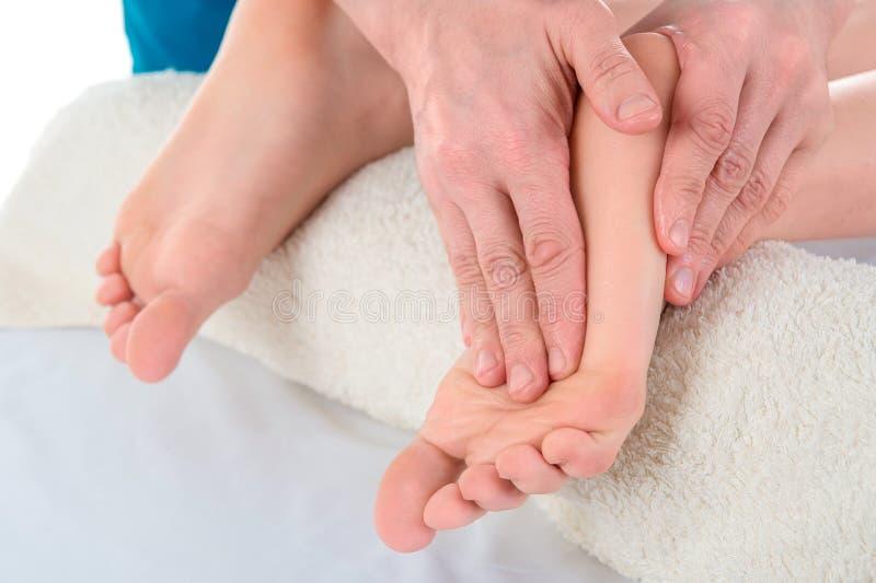 医生足病医生做耐心` s脚的考试和按摩在诊所的 免版税库存照片