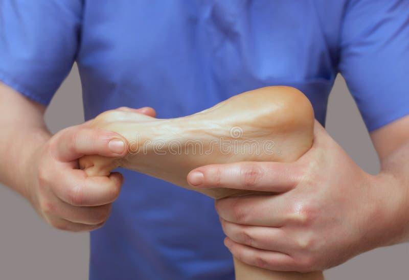 医生足病医生做耐心` s脚的考试和按摩 免版税图库摄影