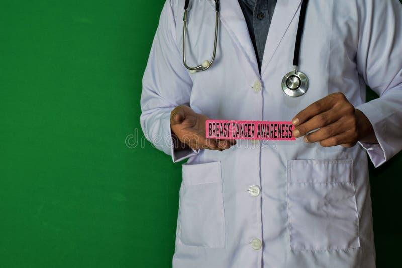 医生身分,拿着在绿色背景的乳腺癌了悟纸文本 医疗和医疗保健概念 免版税库存照片