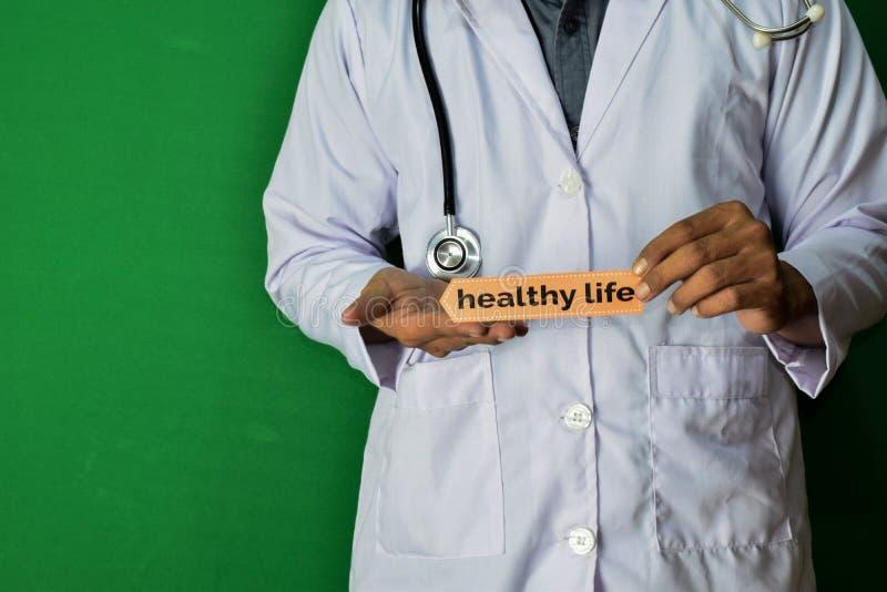 医生身分,拿着在绿色背景的健康生活纸文本 医疗和医疗保健概念 库存图片