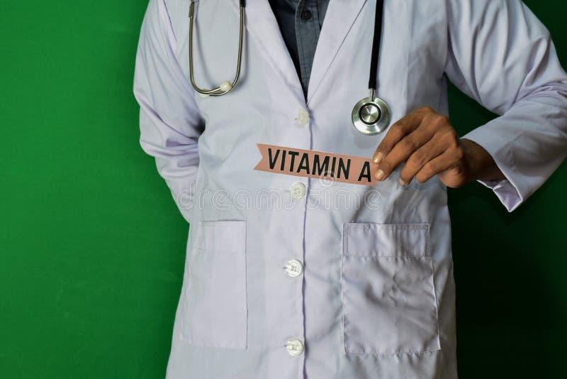 医生身分,拿着在绿色背景的维生素A纸文本 医疗和医疗保健概念 图库摄影