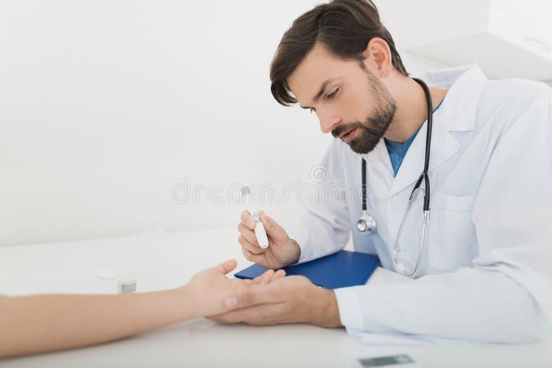 医生采取从男孩的一个血样检查它糖 男孩耐心地忍受做法 免版税库存照片