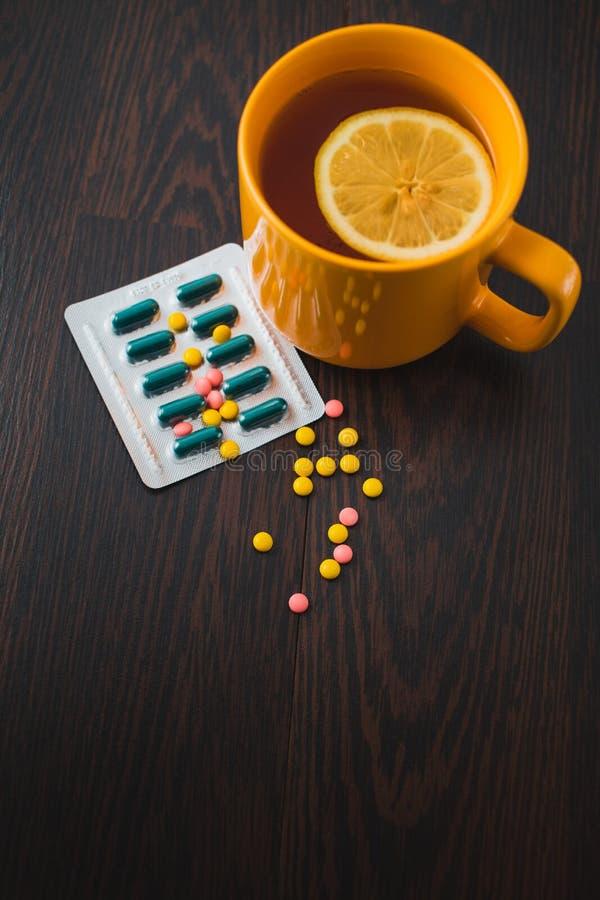医疗保健、传统医学和流感概念-茶杯用柠檬和药片 医疗药片和热的茶用柠檬 库存图片