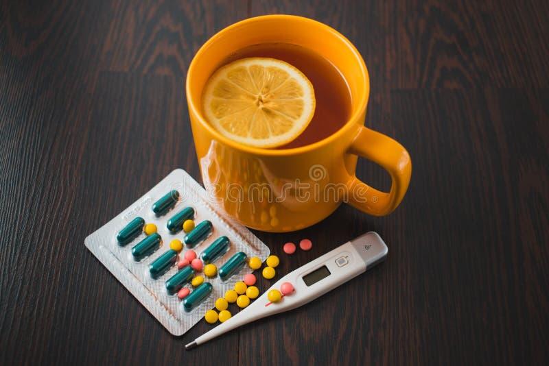 医疗保健、传统医学和流感概念-茶杯用柠檬和药片 医疗药片和热的茶用柠檬 免版税库存图片
