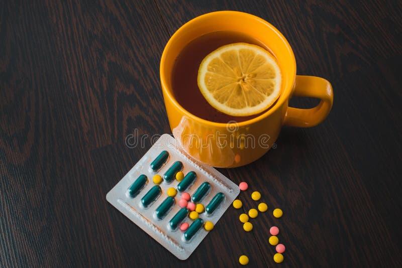 医疗保健、传统医学和流感概念-茶杯用柠檬和药片 医疗药片和热的茶用柠檬 库存照片