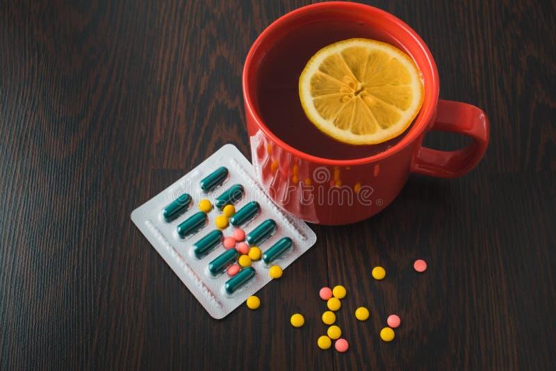 医疗保健、传统医学和流感概念-茶杯用柠檬和药片 医疗药片和热的茶用柠檬 免版税图库摄影