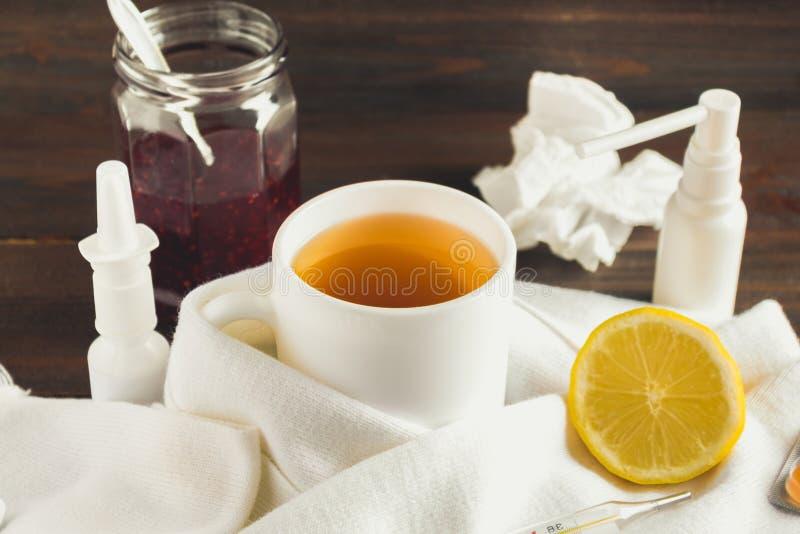 医疗保健、传统医学和流感概念-茶用柠檬、温度计和药物在木桌上 免版税库存图片