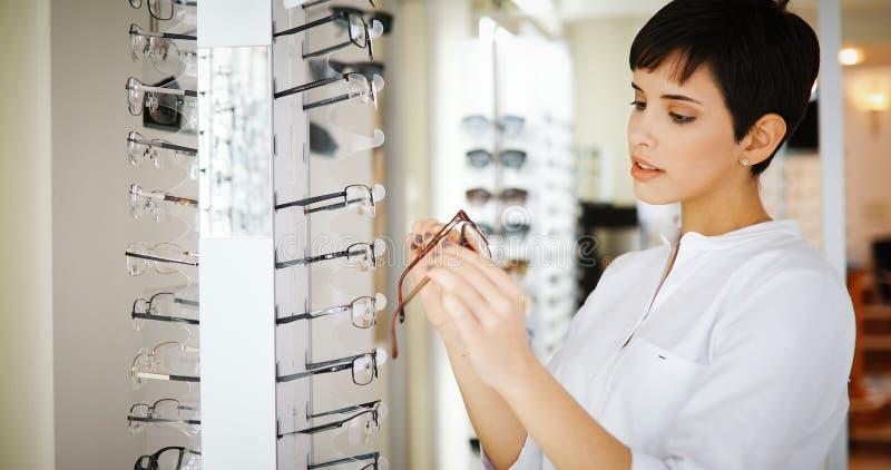 医疗保健、眼力和视觉概念-选择玻璃的愉快的妇女在光学商店 免版税图库摄影