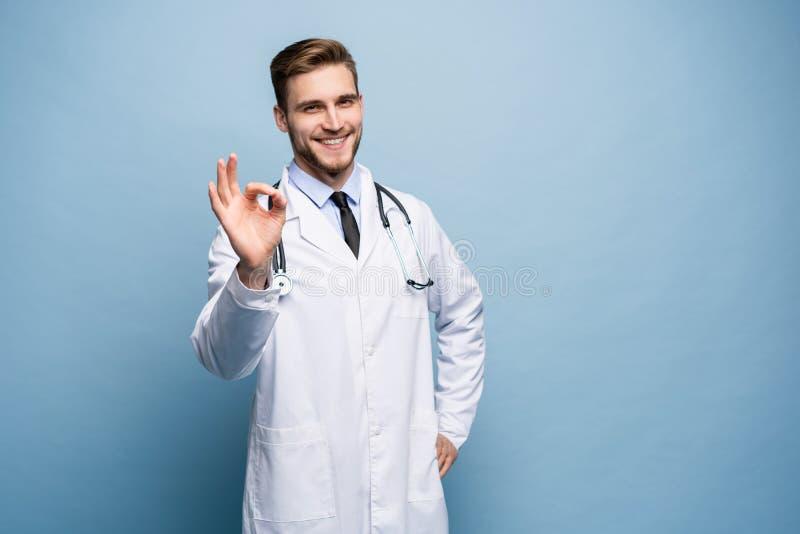 医疗保健、行业、姿态、人和医学概念-显示好手的白色外套的微笑的男性医生签字 免版税库存图片