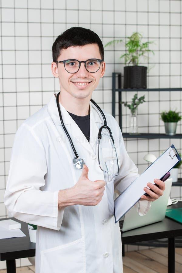 医疗保健、行业和医学概念-显示在医疗办公室背景的微笑的男性医生赞许 免版税库存图片