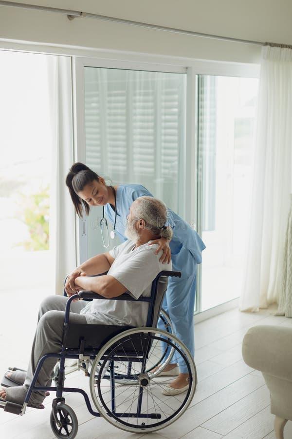 医疗保健工作者谈话与轮椅的人 免版税图库摄影
