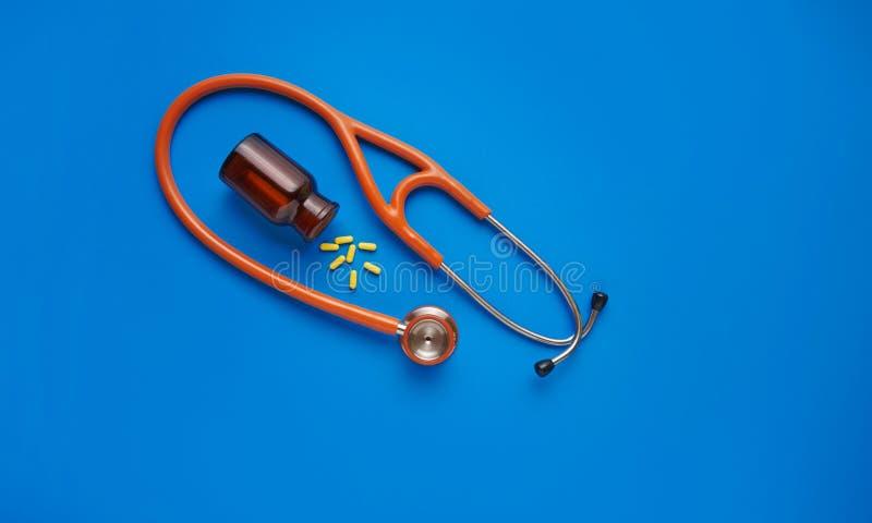 医疗保健概念黄色药片和听诊器在蓝色背景 r 库存照片