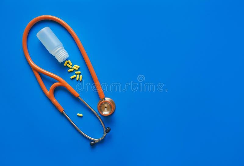 医疗保健概念黄色药片和听诊器在蓝色背景 r 图库摄影