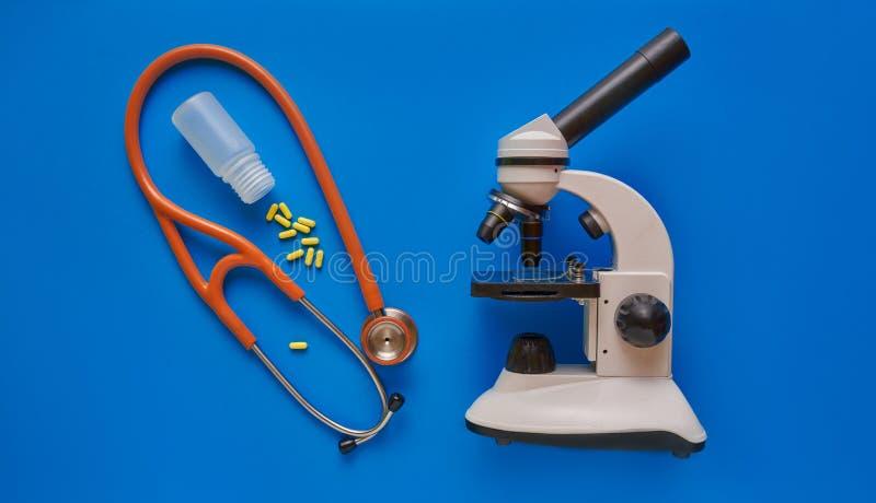 医疗保健概念黄色药片和听诊器在蓝色背景 r 库存图片