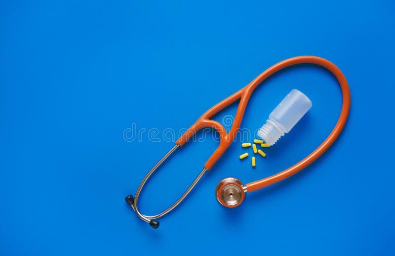 医疗保健概念黄色药片和听诊器在蓝色背景 r 免版税库存照片