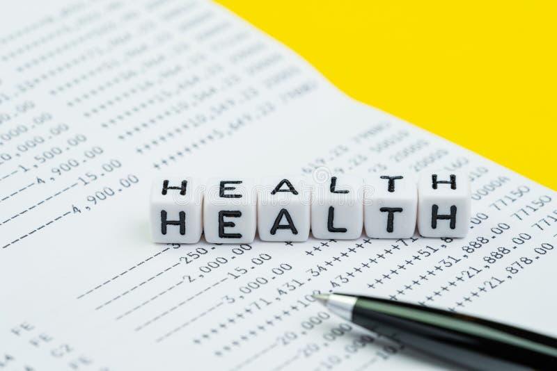 医疗保健费用、费用或者储款个人保险概念的,立方体块与建立词健康与笔的字母表 免版税库存图片
