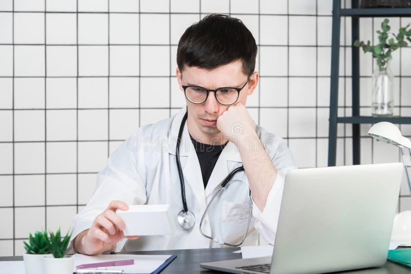 医疗保健,医疗和药房概念-有盒的男性医生药片 库存图片