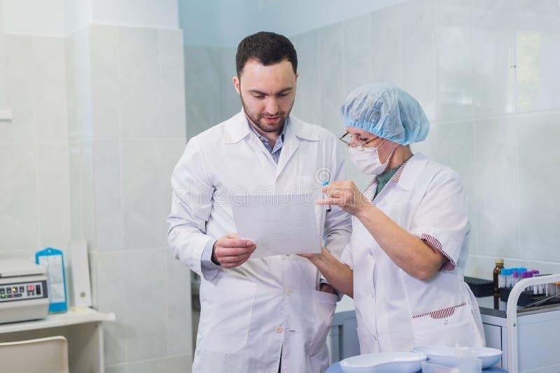 医疗保健:谈论的医生和的患者血液测试结果 免版税库存照片