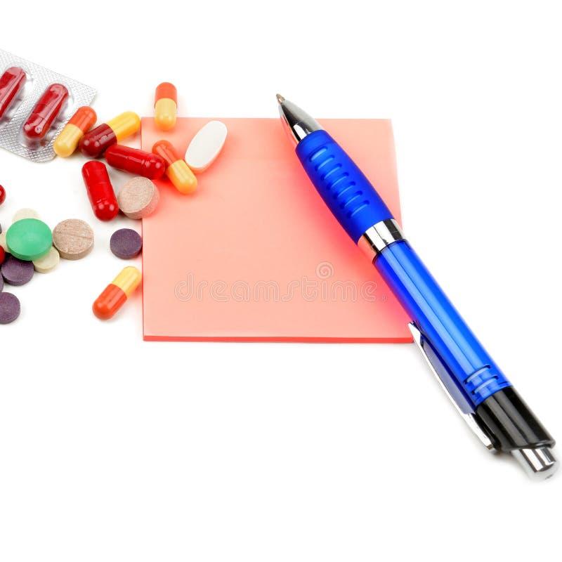 医疗准备、药片胶囊、空的处方和在白色背景隔绝的圆珠笔 库存图片