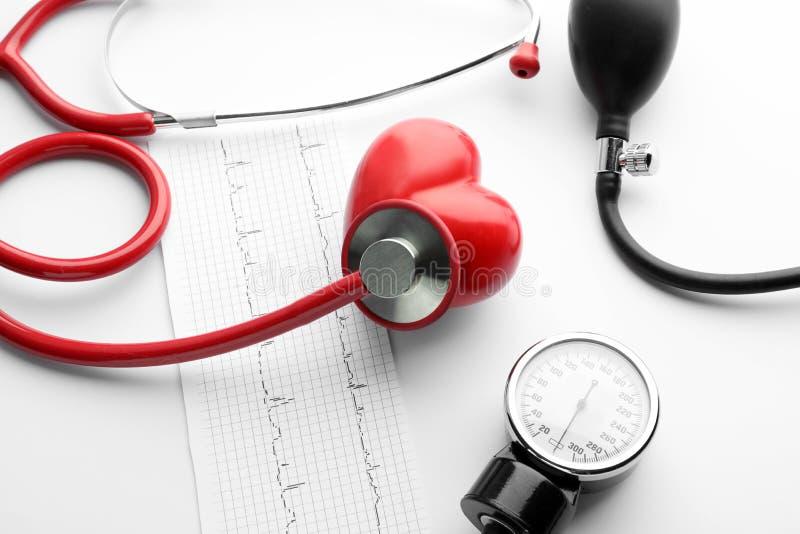 医疗听诊器、血压计、心电图和红心在白色背景 E 库存图片