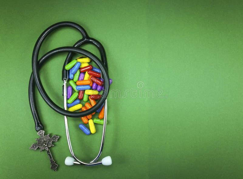 医疗听诊器和基督徒耶稣受难象有药片的 免版税库存照片