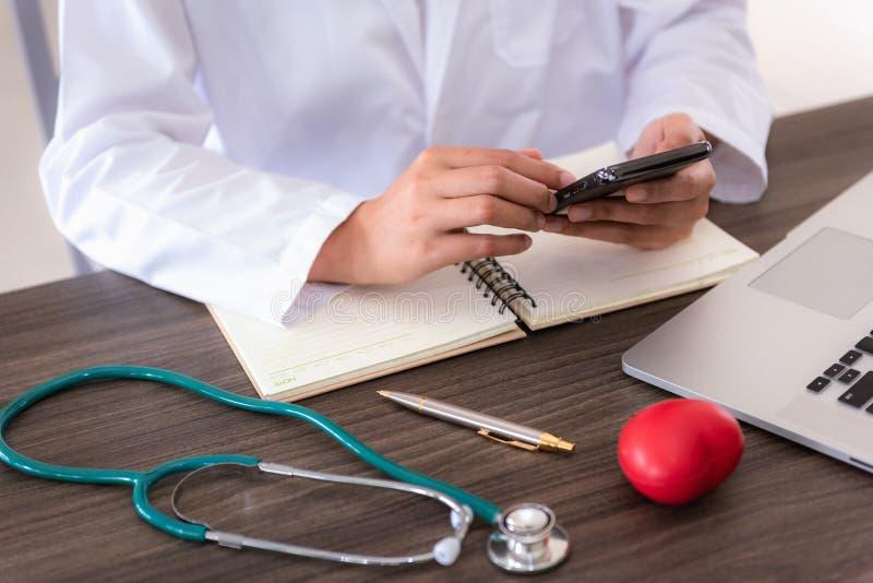医疗女性医生在考试屋子里时使用手机,当等待她的患者 免版税库存图片