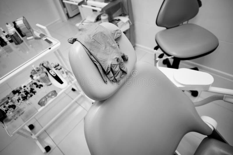 医疗手套垂悬在牙齿椅子,医疗办公室背面 库存图片