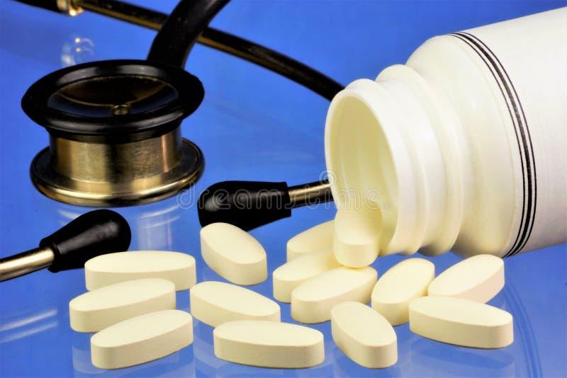 医疗疗程药片和听诊器在蓝色背景 医生诊断,听诊器听症状,规定 库存照片
