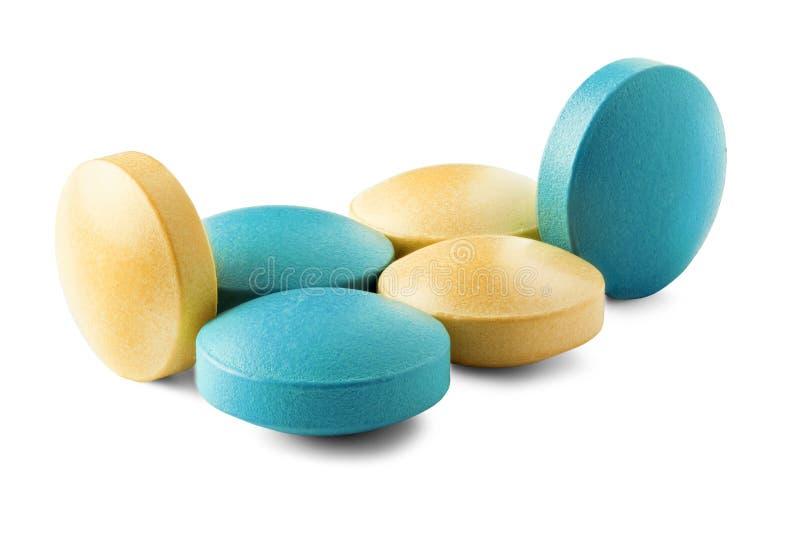 医疗药片堆在黄色和绿色的,与在被隔绝的白色背景的阴影 与圆形的药片 库存图片